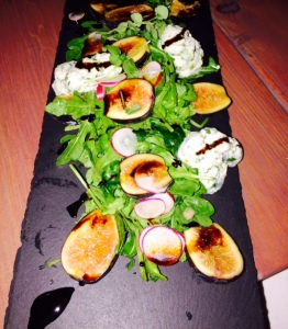 A delicious salad of mission figs, arugula, radishes, prosciutto and whipped ricotta is beautifully presented on black slate. Photo by Jill Weinlein