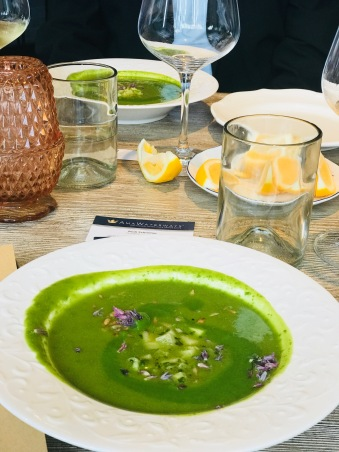 verdant asparagus and kohlrabi soup enhanced with ginger, sunflower seeds and chive blossoms